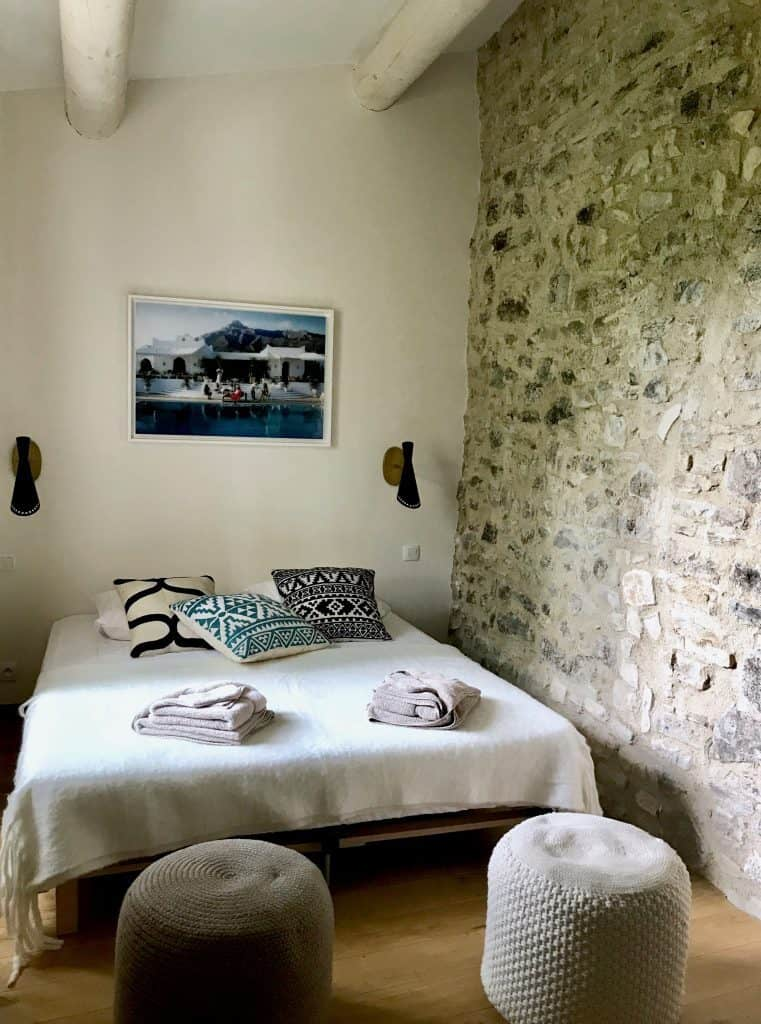 bedroom with original stone wall in French farmhouse manor in Provence
