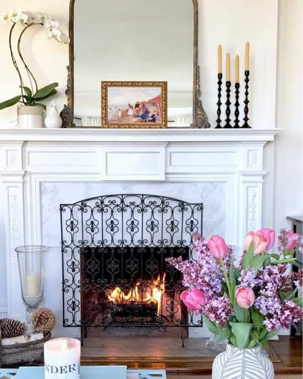 symmetrical orchid and candle sticks on mantel