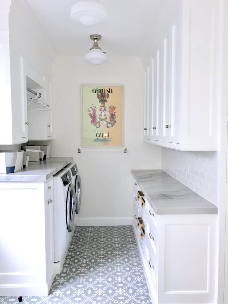 Classic Laundry Room with white cabinets and marble counters