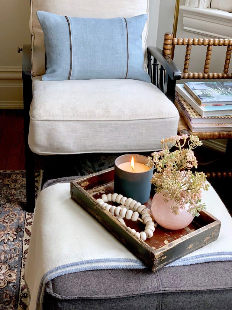 A rustic box becomes a stage for a chic vignette with pink, beads, and candlelight - design by Classic Casual Home's Mary Ann Pickett. Come discover more inspiring trays for layering and vignettes in Adding Tray Très Chic to Your Home.