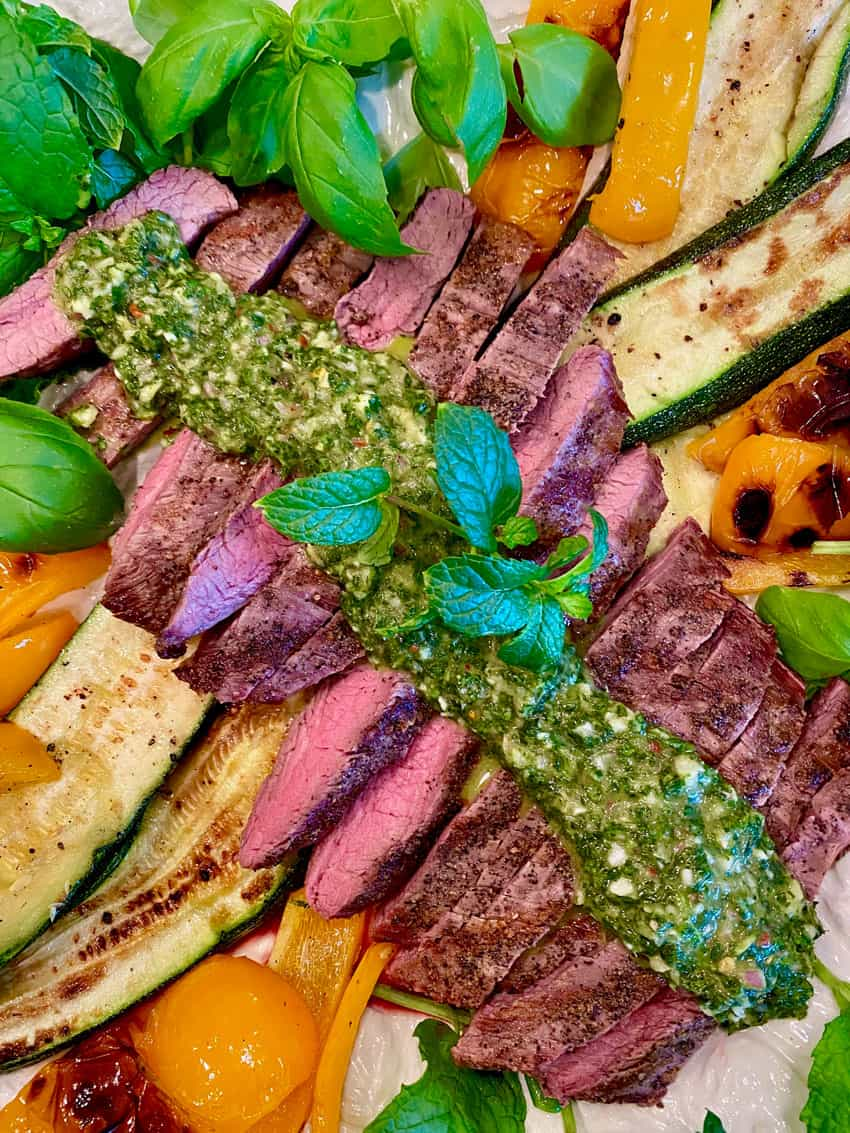 closeup of chimichurri sauce drizzled on sliced steak