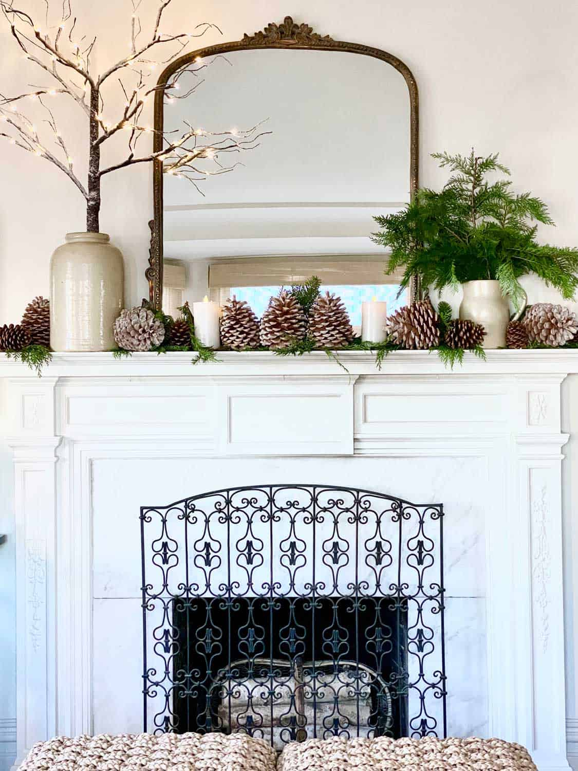 Mary Ann Pickett's White Fireplace decorated for Christmas with pinecones and branches