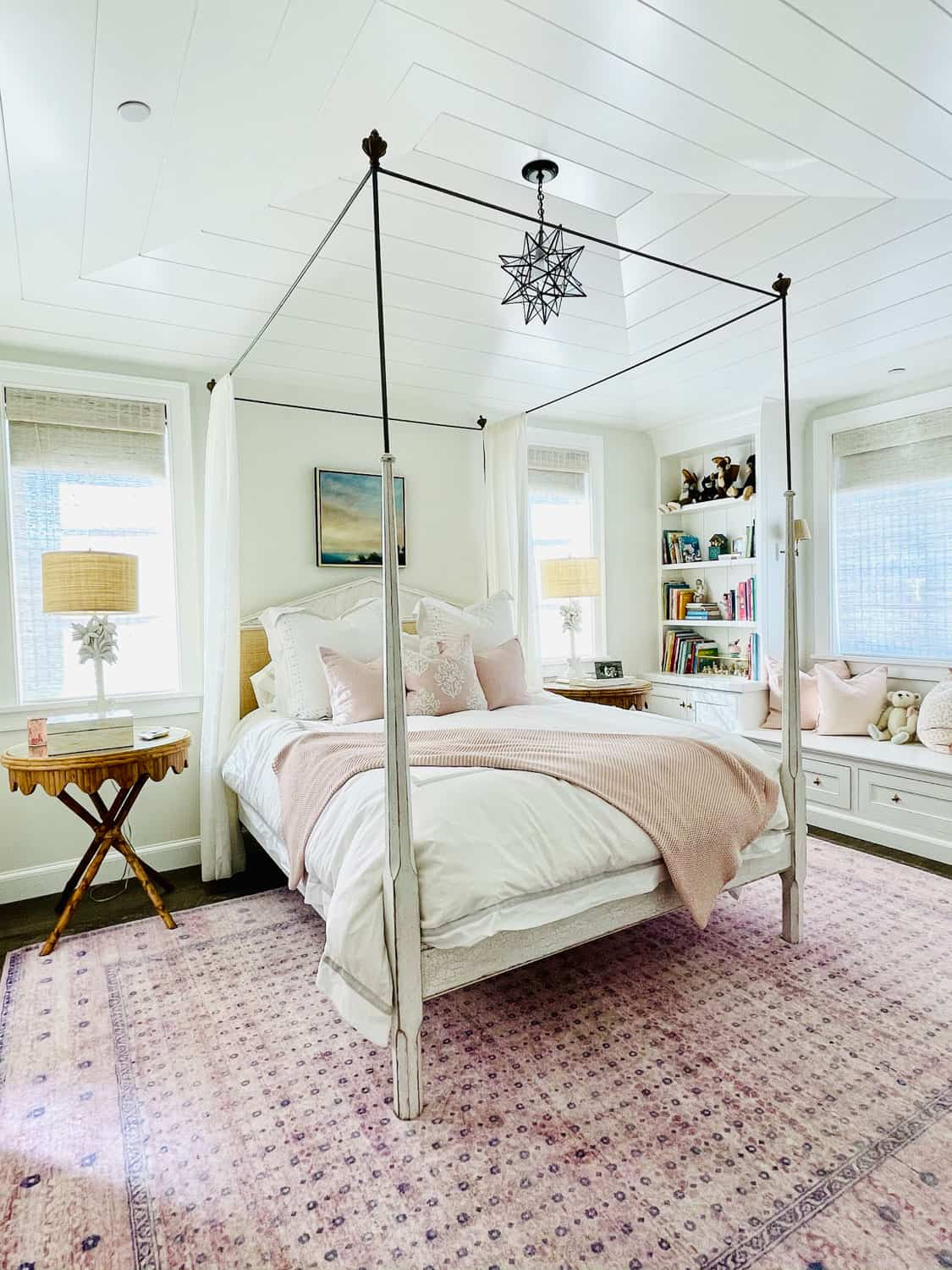 white four poster bed with pink rug