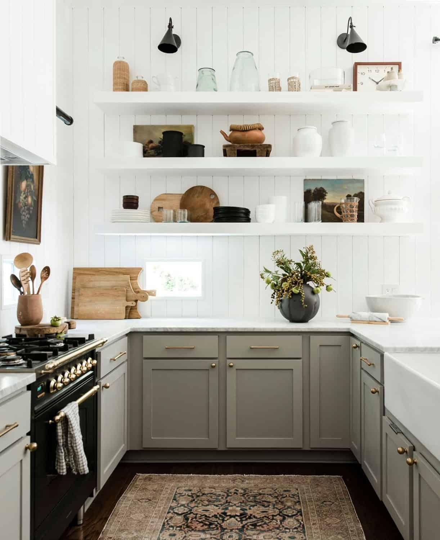 vintage rug, white open shelves, sage green cabinets