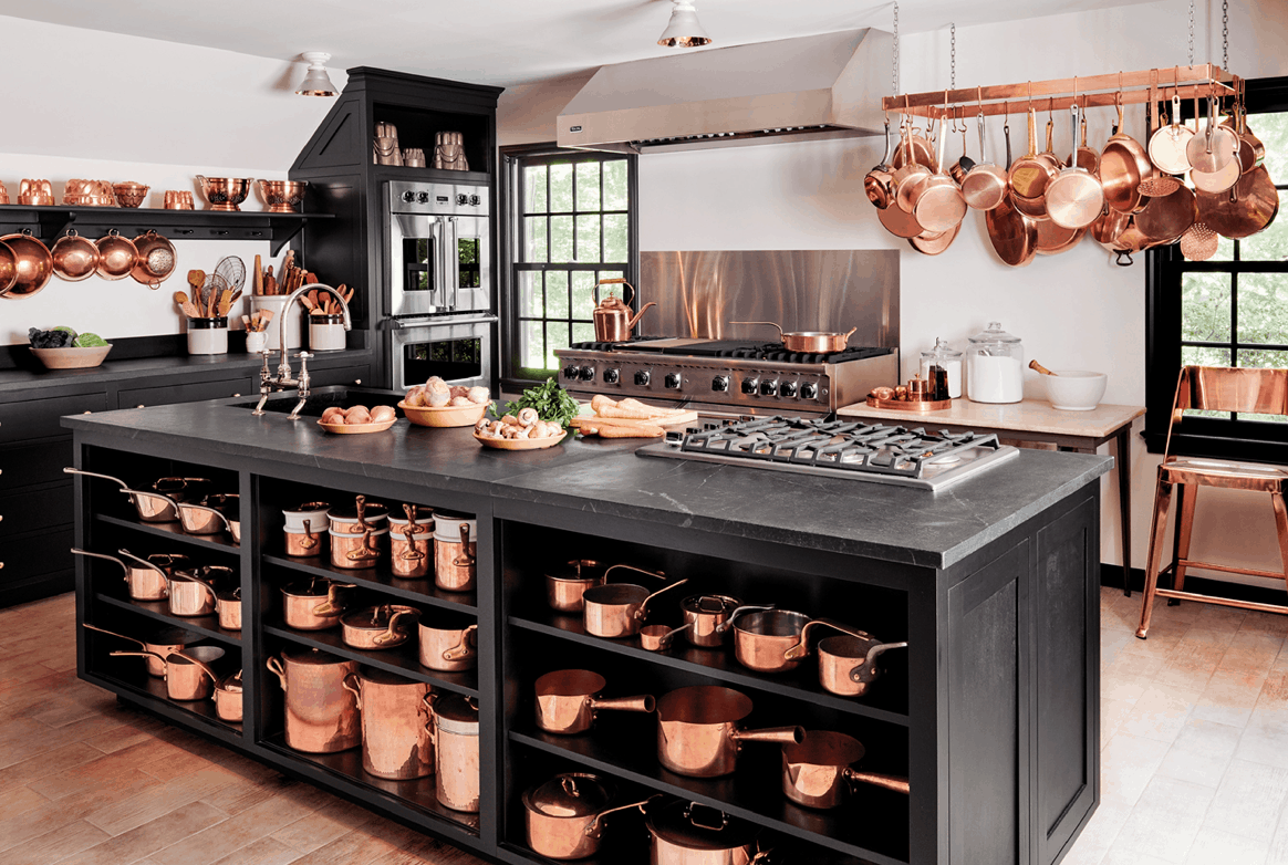 Martha Stewarts kitchen with black cabinets and copper pots